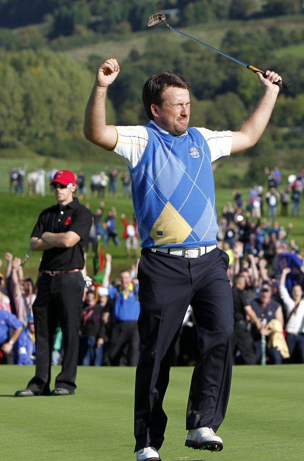 Graeme McDowell celebrates on the 16th green after making birdie in his singles match against Hunter Mahan, pictured in the background.