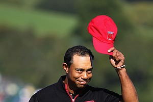 Tiger Woods doffs his cap after holing out for eagle on the 12th hole during Ryder Cup singles. In arguably his most dominant round of 2010, Woods claimed a 4-and-3 win over Francesco Molinari.