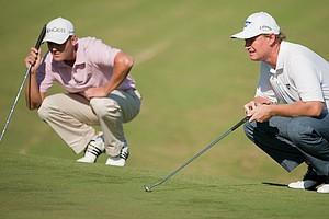 Martin Kaymer and Ernie Els read their putts on the first green at Port Royal Golf Course.
