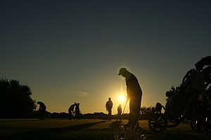 Junior golfers practice putting in the chilly temperatures as the sun rises Saturday morning.