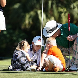 PGA Tour player Rory Sabatini, right, helps his son, Harley, 7, center, and Ben Curtis' children, Addison, 2, left, and Liam, 4, right, with candy at the final hole.