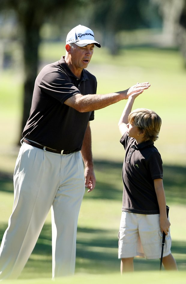 Tom Lehman gives a high five to his son, Sean after his chip shot at No. 3.