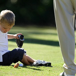 Henry Davis, 4, son of PGA Tour player, Brian Davis, looks for his ball after checking the yardage at the first hole.