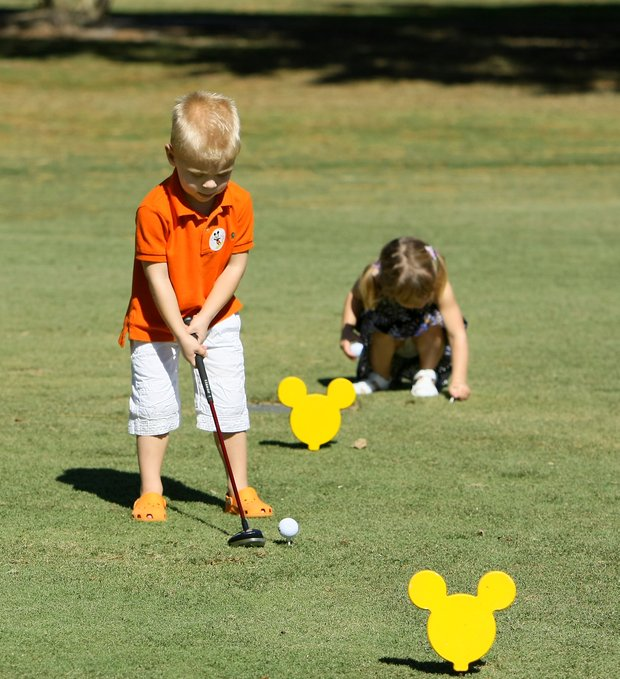 Liam Curtis, 4, son of Ben Curtis, prepares to his his tee shot on the Oak Trail course.