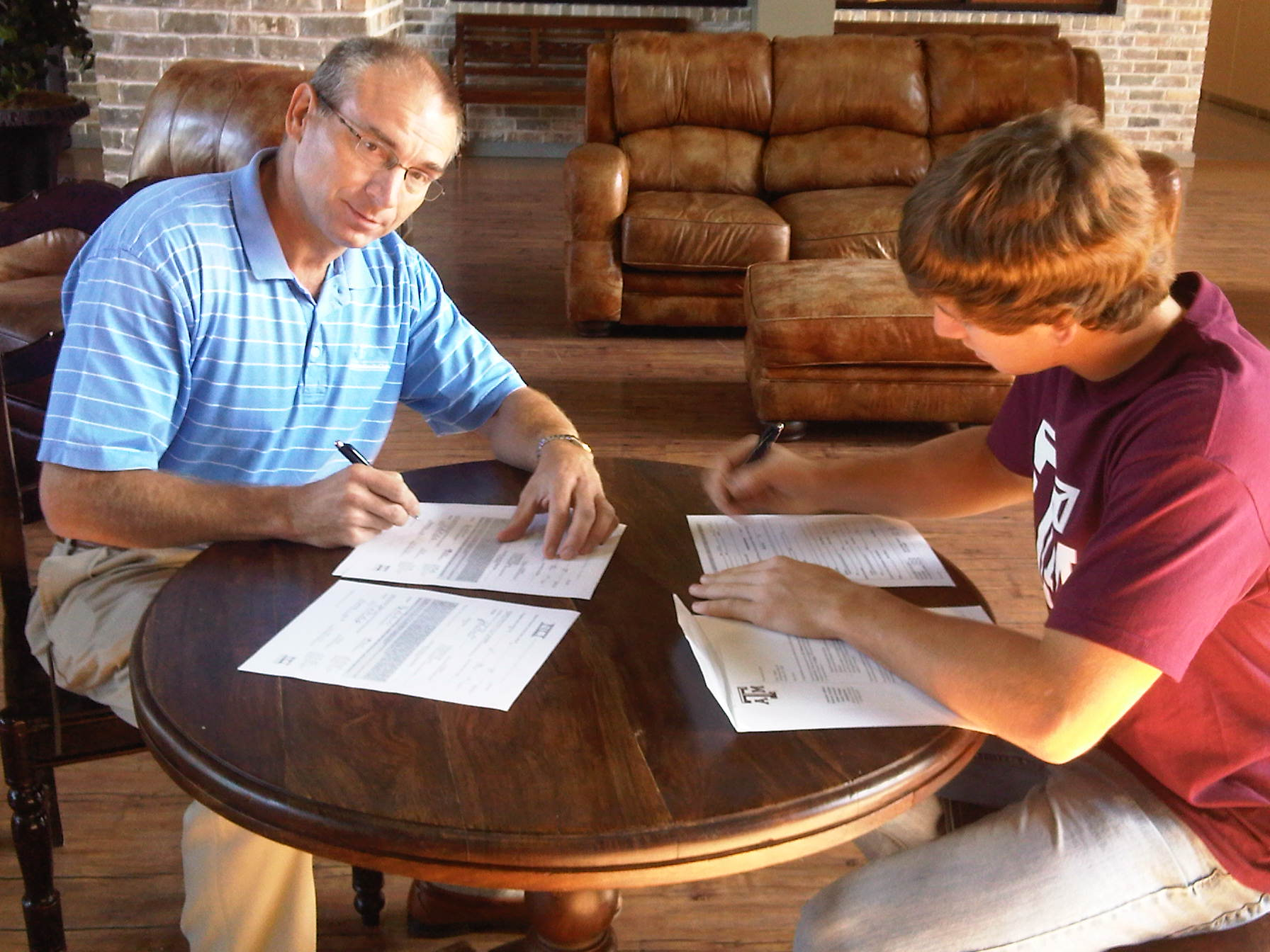 Tyler Dunlap and his father signing a letter of intent with Texas A&M