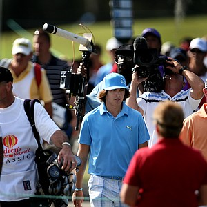 Rickie Fowler, center, and Skip Kendall, right, try to make their way to the 18th tee.