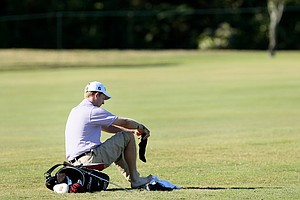 Michael Connell puts his socks and shoes back on after hitting out of the hazard at No. 17.