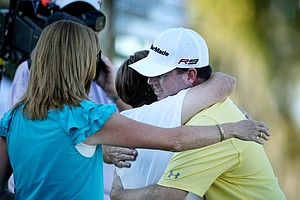 Robert Garrigus gets a hug from his mom, Linda Cox, and sister, Chris Dye at No. 18.