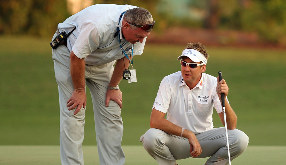 European Tour referee Andy McFee talks to Ian Poulter on the 18th green at Dubai.