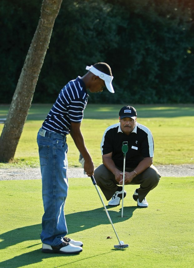 Adrian Stills instructs Devin Collins during a First Tee event at Osceola Golf Course.