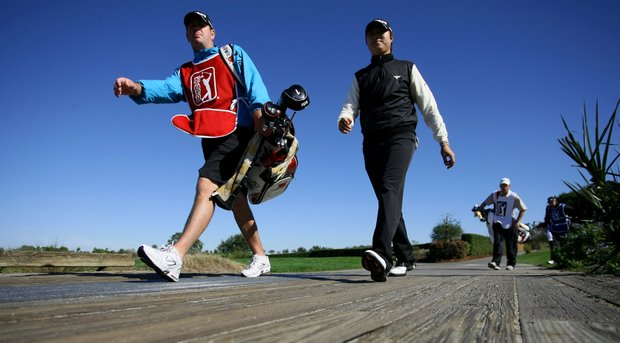 Seong Ho Lee of Seoul, Korea, along with his caddie makes his way to the third fairway on Panther Lake.