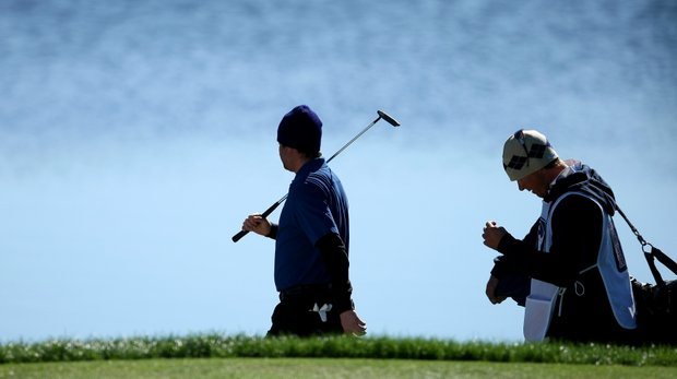 Nate Smith and his caddie are silhouetted as they walk along the water at No. 9 on Panther Lake.