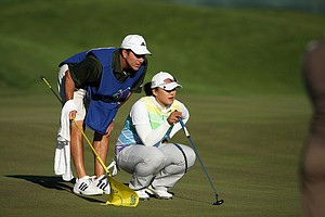 Amy Yang and her caddie read a putt during the final round of the LPGA Tour Championship.