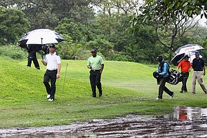 Players return to the clubhouse as rain stops play during Round 1 of the South African Open.