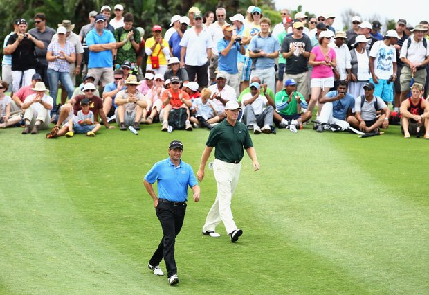 Retief Goosen (L) is followed by Ernie Els of South Africa on the 18th during round three of the South African Open Golf Championship at the Durban Country Club on December 19, 2010 in Durban, South Africa.