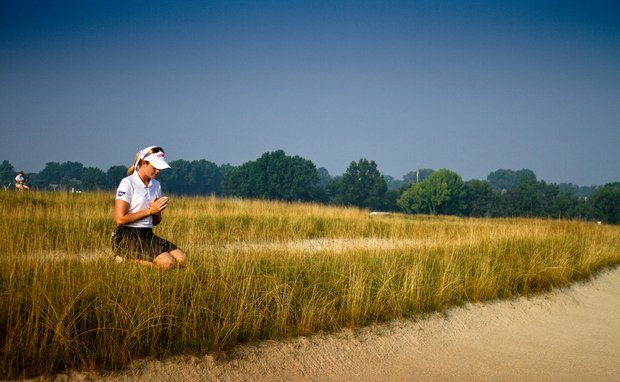 "Paula Creamer kneels at Oakmont's ""church pew bunkers."""
