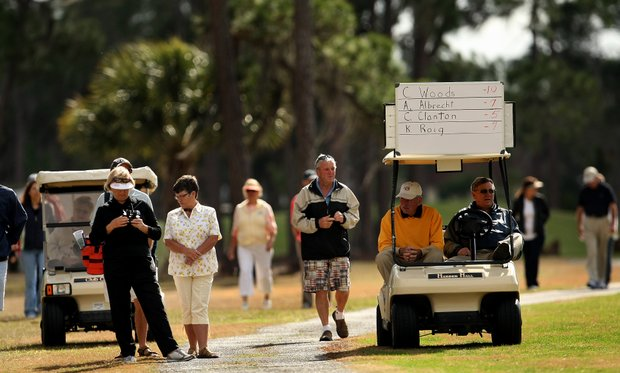 A small gallery follows the final group and the scoring cart during the third round.