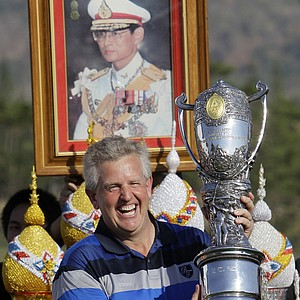Europe team captain Colin Montgomerie celebrates while holding the Royal Trophy in front of a portrait of Thai King Bhumibol Adulyadej after defeating the Asia team on Sunday, Jan. 9 in  Hua Hin, Thailand.