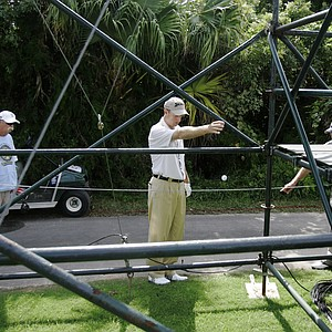 Golfer Jim Furyk , center, takes relief from a cart path to set up a another drop away from a television tower on the 11th hole during the PGA Grand Slam of Golf tournament Wednesday, Oct. 17, 2007, in Tucker's Town, Bermuda. At left is Furyk's caddie Mike Cowan, and PGA rules official Mark Wilson.