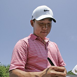 Anthony Kim autographs a picture for a fan during a practice round at The Players Championship golf tournament in Ponte Vedra Beach, Fla., Wednesday, May 7, 2008. Kim is coming off his win in the Wachovia Championship