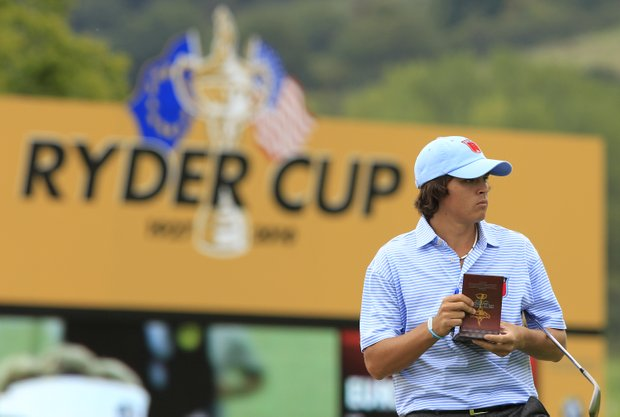 Rickie Fowler looks at his notebook on the 14th fairway during a practice round at the 2010 Ryder Cup golf tournament in Newport, Wales, Tuesday, Sept. 28, 2010.