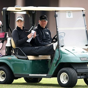 Brittany Lincicome and her friend, Nick Frontero, right, wait in a cart during Lincicome's opening round at Deer Island.
