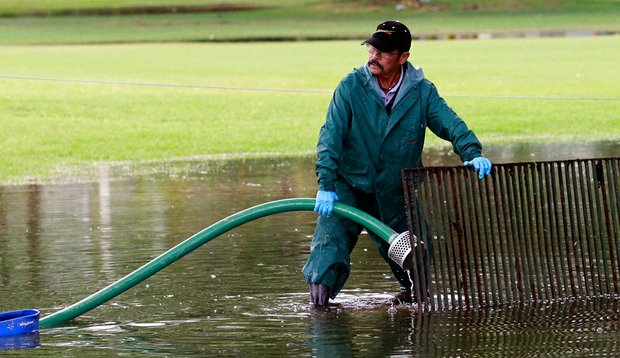 Grounds crew personnel pumps water from the 10th hole after heavy rains forced the cancellation of the first round of the Sony Open at Waialae Country Club.