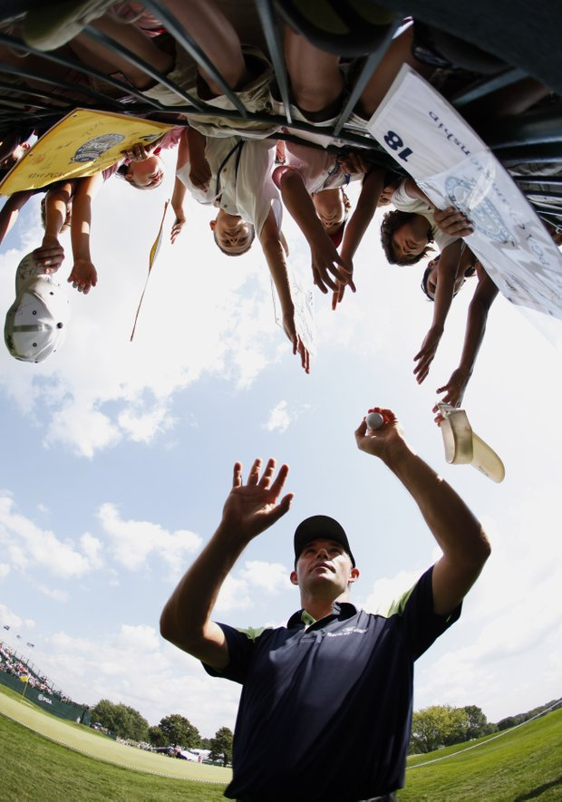 Padraig Harrington, of Ireland, hands out golf balls to spectators following his practice round for the 91st PGA Championship at the Hazeltine National Golf Club in Chaska, Minn., Wednesday, Aug. 12, 2009.