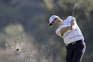 Padraig Harrington of Ireland hits his approach shot to the 18th green in the second round of the Chevron World Challenge golf tournament at Sherwood Country Club in Thousand Oaks, Calif., Friday, Dec. 4, 2009. Harrington finished the day at 7-under-par 137, in a three-way tie for second, two strokes behind leader Y.E. Yang.