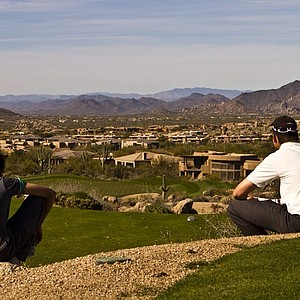 Golfers sit on top of a hill and look over the Troon North Monument Course during the Golfweek West Coast Junior Invitational in Scottsdale, Ariz.