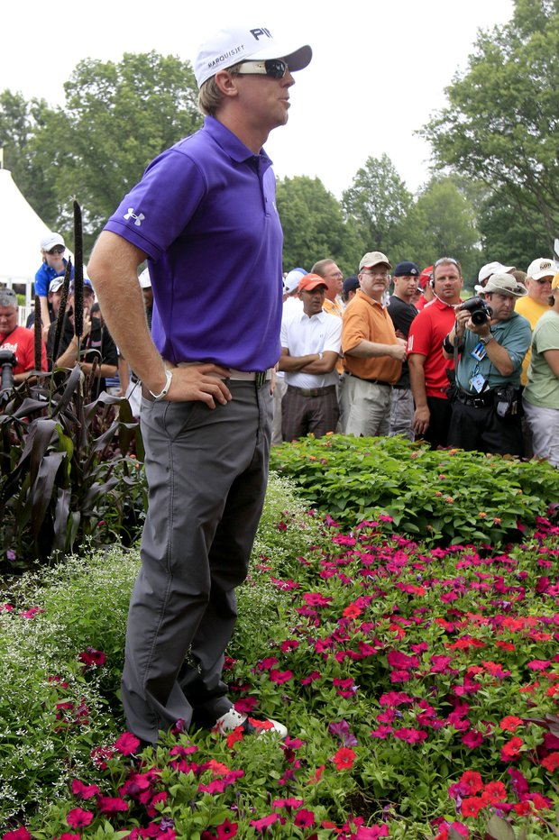 Hunter Mahan stands in a flower bed behind the 16th green after finding his ball and planning his shot during the final round of the Bridgestone Invitational at Firestone Country Club in Akron, Ohio, Aug. 8, 2010. Mahan went on to win the tournament.