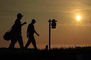 Hunter Mahan, left, and Tiger Woods walk off the second tee during a practice round at the PGA Championship at Whistling Straits in Haven, Wis., Aug. 10, 2010.