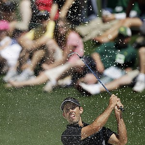 Charl Schwartzel of South Africa is showered with sand after hitting out of a trap on the second hole during the final round of the Masters golf tournament in Augusta, Ga., Sunday, April 11, 2010.