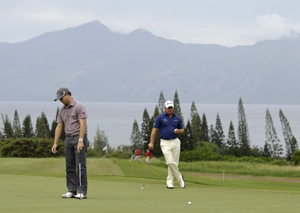 Zach Johnson, left, reacts after missing a birdie putt on the third green as Graeme McDowell, right, of Northern Ireland, looks on during the second round of the Hyundai Tournament of Champions golf tournament in Kapalua, Hawaii, Friday, Jan. 7, 2011.