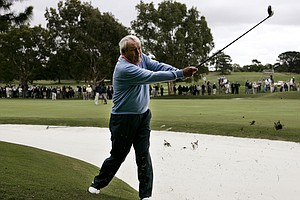 Arnold Palmer watches his shot during an exhibition match with Australian golfers Peter Thomson and Bruce Devlin at the Australian Golf Club in Sydney, Nov. 24, 2004.