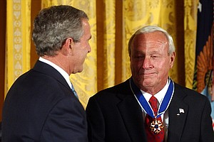 Former President George W. Bush presents Arnold Palmer, right, with the Presidential Medal of Freedom, the nation's highest civil award, during a ceremony at the White House, June 23, 2004.