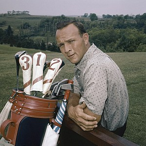 Golf legend Arnold Palmer poses with this golf clubs in this undated photo.