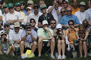Spectators watch as Arnold Palmer tees off from the ninth hole during the par-3 tournament at the Masters in Augusta, Ga., April 7, 2010.