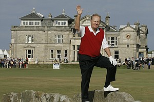 Jack Nicklaus waves from the Swilcan Bridge as he makes his way to complete his final round ever in the British Open, on the Old Course at St. Andrews, Scotland, July 15, 2005.