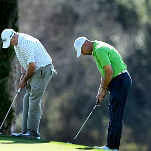 Ted Potter, left, and Cliff Kresge, right, practice their putting stroke at No. 10.