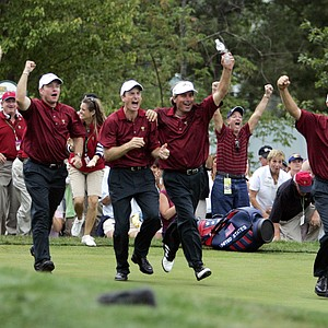 Members of the U.S. team, Justin Leonard, left, Scott Verplank, second from left, Jim Furyk, center, Fred Couples, second from right, and Davis Love III, right, charge onto the 18th green after Chris DiMarco won his match against Stuart Appleby of Australia to give the Americans the Presidents Cup singles Sunday, Sept. 25, 2005, at the Robert Trent Jones Golf Club in Gainesville, Va.