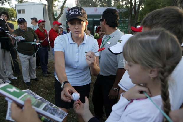 United States' Cristie Kerr, center, signs autographs to fans after the first round of the Lorena Ochoa Invitational LPGA golf tournament in Guadalajara, Mexico, Thursday Nov. 11, 2010.
