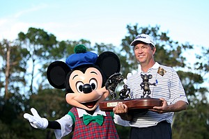 Davis Love III poses with Mickey Mouse after winning the Children's Miracle Network Classic in Lake Buena Vista, FL.