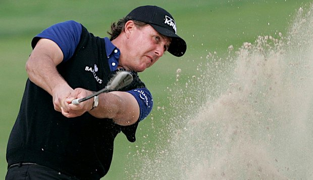 Phil Mickelson blasts out of a bunker at Abu Dhabi Golf Club.