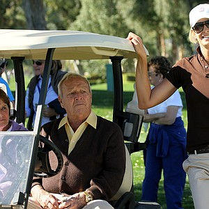 Arnold Palmer talks with Angie Watson, wife of PGA Tour golfer Bubba Watson, on the 16th hole during Round 2 of the Bob Hope Classic at the La Quinta Country Club
