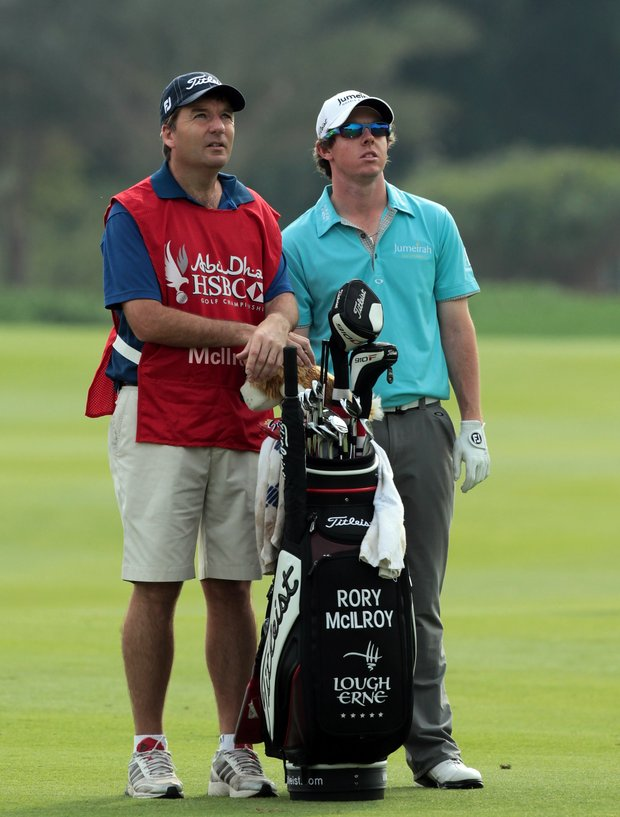 Rory McIlroy of Northern Ireland waits to play his second shot at the 13th hole with his caddie J.P. Fitzgerald during the third round of the 2011 Abu Dhabi Golf Championship.