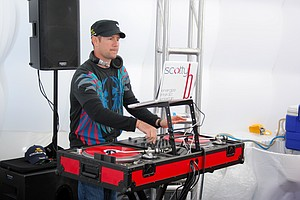 A disc jockey plays music at the Cobra-Puma booth on Demo Day of the PGA Merchandise Show.