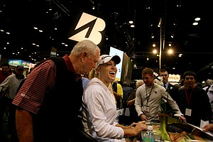 Teaching pro Butch Harmon and LPGA player Natalie Gulbis spent an hour at the Winn Grips booth signing autographs Thursday afternoon. The line – perhaps 100 or so – snaked around the booth. Gulbis signed posters and chatted as cell-phone cameras captured the occasion.