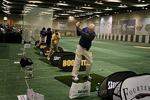 Jerry Crow from Asheville, N.C., tries out a Bridgestone J38 6-iron at the indoor range on the floor of the PGA Merchandise Show.