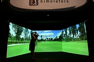Tyler Brandeburg, of Lady Lake, Fla., tests out a PGA Tour SimSurround simulator from aboutGolf. The company displayed both the SimSurround and Classic models on the show floor, both of which are performance-oriented simulators.